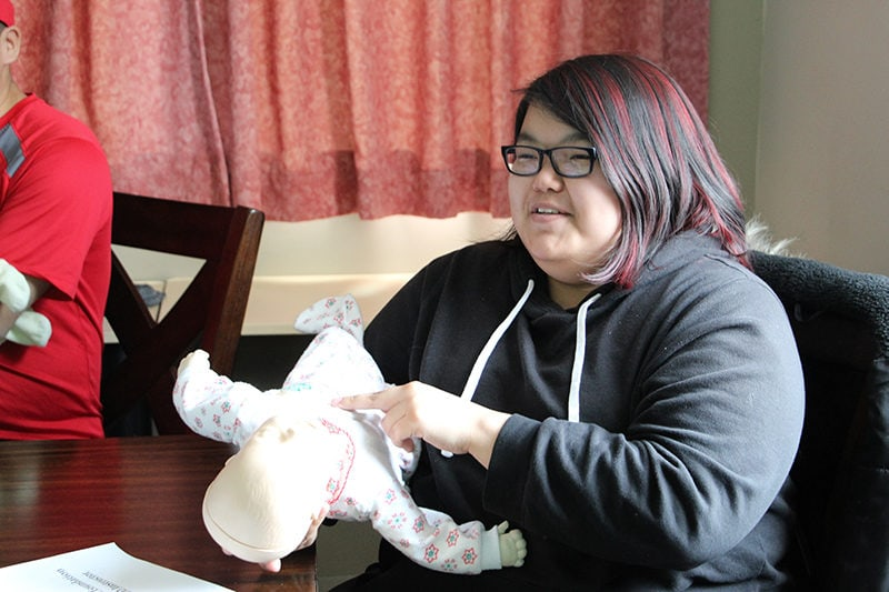 Inuit woman holding a CPR dummy